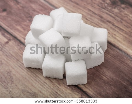 Sugar cubes over wooden background - stock photo