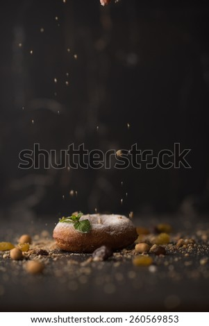 Sugar Donut sprinkled with crumbs on dark stone background  - stock photo