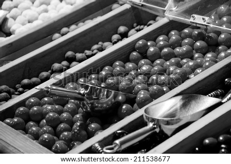Sugar iced chocolate balls and other candies in candy shop. Selective focus on the chocolate balls. Aged photo. Black and white. - stock photo