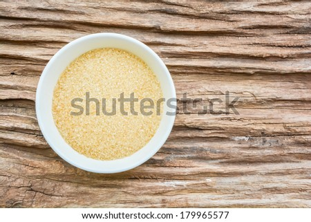 Sugar in cup place on old wooden - stock photo