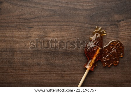 sugar lollipop rooster shaped on wooden table - stock photo
