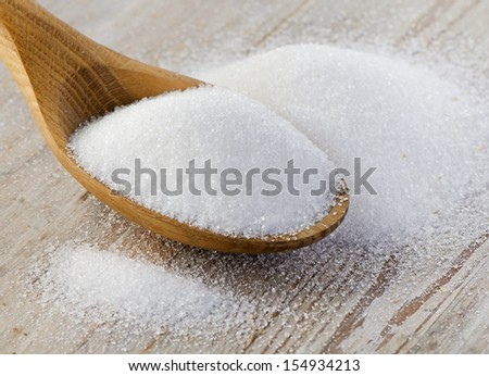 Sugar on wooden table. Selective focus - stock photo