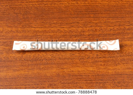 Sugar packet on a wooden table - stock photo