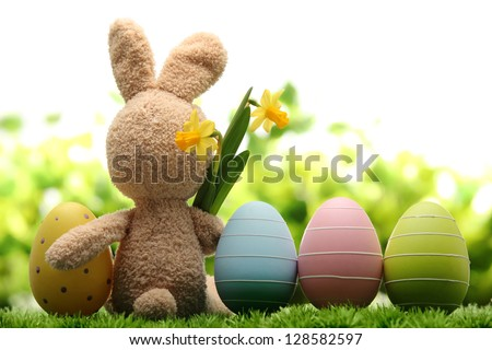 Sugar rabbit and easter eggs on meadow. - stock photo