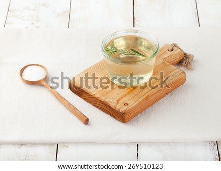 Sugar syrup with rosemary p in a glass bowl on a white wooden background - stock photo