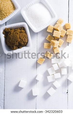 sugar variation on white wood table background - stock photo