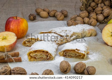 Sugared Homemade Apple Strudel on Baking Paper with Walnuts, Cinnamon and Apple - stock photo
