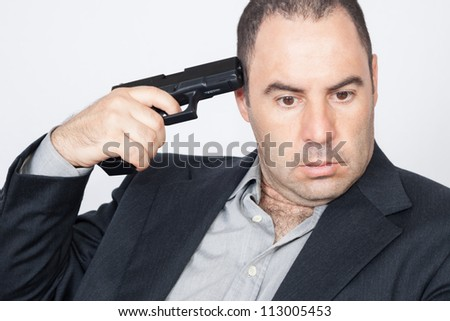 Suicide concept - man pointing a gun at his head - stock photo