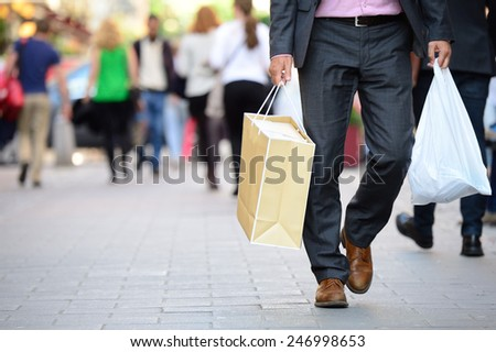 Suit with shopping bags on shopping street - stock photo