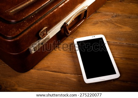 Suitcase and old camera, tablet, phone and a cup of coffee. - stock photo
