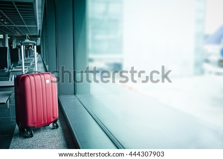 Suitcase in airport in the waiting hall  - stock photo