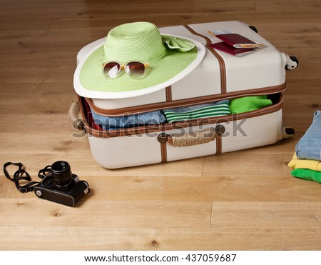 Suitcase on a floor with clothing, tickets, passport and sunglasses. Luggage ready to travel. - stock photo
