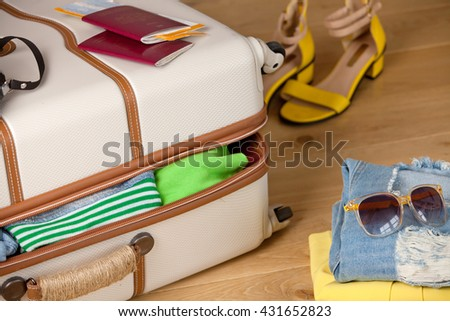Suitcase on a wooden floor with clothing, tickets, passport and sunglasses. Luggage ready to travel. - stock photo