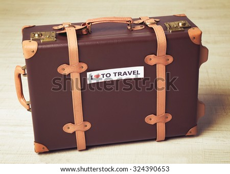 Suitcase with sticker on floor in room - stock photo