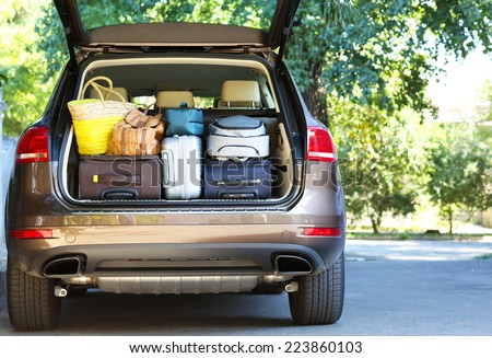 Suitcases and bags in trunk of car ready to depart for holidays - stock photo