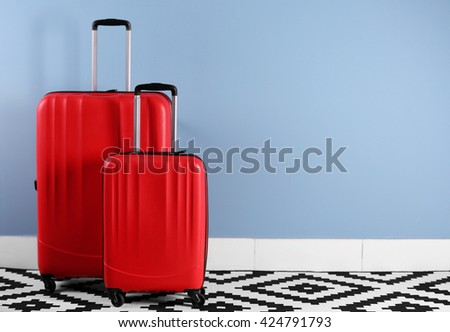 Suitcases on blue wall background - stock photo
