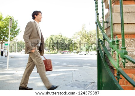 Suited businessman walking fast through the city on his way to work and carrying a briefcase, outdoors. - stock photo