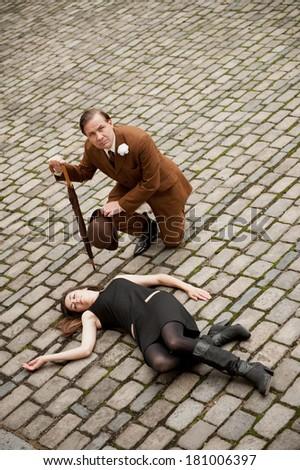 Suited Man Kneeling By Fallen Woman - stock photo