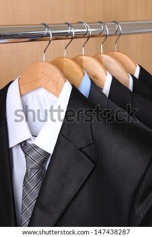 Suits with shirts on hangers on wooden background - stock photo