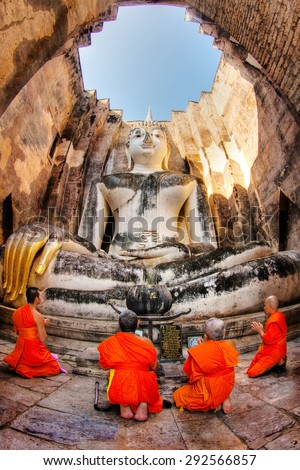SUKHOTHAI,THAILAND-NOV 9 , 11: Thai monks pray Buddha statue at Wat Sri Chum on November 9, 2011 in Sukhothai, Thailand. Here, Found in 1930 century, has large buddha statue called Phra Atchana. - stock photo