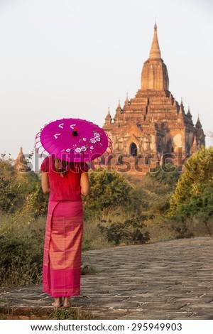 Sulamani Temple, Nyaung-U, Myanmar (Burma). A woman wearing traditional Burmese clothing watches the sunrise on Sulamani Temple. - stock photo
