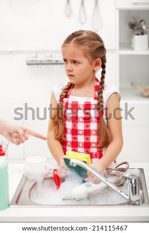 Sulking little girl doing the dishes on parents order - stock photo
