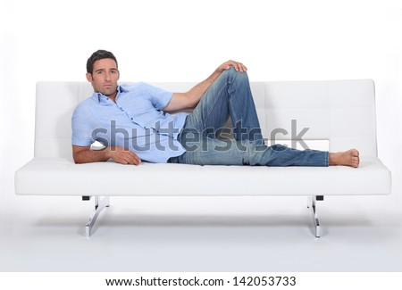 Sulky man lying on a couch - stock photo