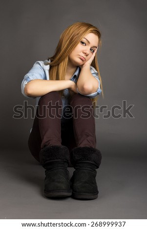Sulky teenage girl sitting on the floor over gray background - stock photo