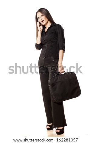 Sulky woman holding a laptop bag and talking on the phone - stock photo