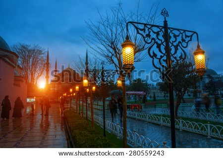 Sultan Ahmed Blue Mosque in Istanbul, Turkey - one of the most popular landmarks in the city. Park, lighted street lamps at night. Sun setting down behind the mosque, sunlight and blurred people - stock photo