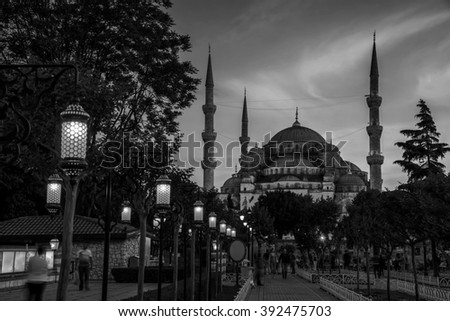 Sultan Ahmed Blue Mosque in Istanbul, Turkey - one of the most popular landmarks in the city. Park, lighted street lamps at night and sunset sky, blurred people. Black and white - stock photo