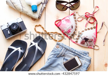 Summer accessories for travel or vacation concept. Vintage camera, denim shorts glasses, bikini, flip flop, beach towel,  sunburn lotion,  mobile on wooden background.  - stock photo