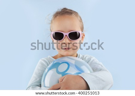 Summer. Adorable beautiful girl with ball and sunglasses against blue background. Summer background. - stock photo