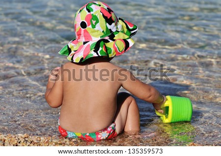 summer baby playing in the sea - stock photo