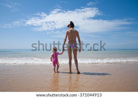 summer back family of two years old blonde baby with pink and yellow swimsuit holding hand with brunette woman mother in bikini standing at sea shore beach sand in Cadiz Andalusia Spain - stock photo