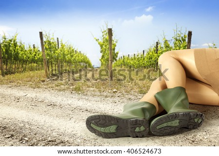 summer background of vineyard and woman on road and green big shoes  - stock photo