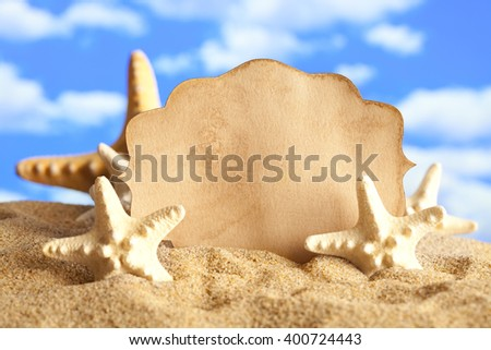 Summer background - paper label and shells on the beach - stock photo