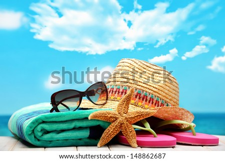 summer beach accessories on sandy beach - stock photo