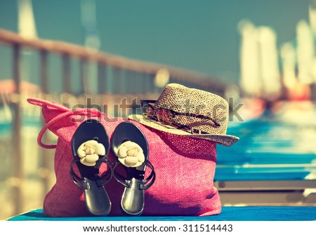 Summer beach bag  , Straw hat, bag, sun glasses and flip flops on a tropical beach  . Summer holiday vacation concept. View from above - stock photo