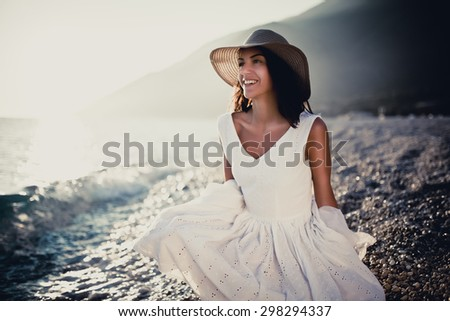 Summer beach fashion woman in white dress enjoying summer and sun,walking the beach near blue sea.Relaxed emotional sensual woman.Travel and vacation.Freedom,inspiration,summer feeling and happiness - stock photo