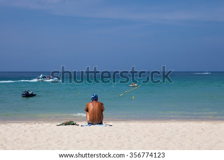 summer beach man sitting and relaxing , Phuket Island in thailand - stock photo
