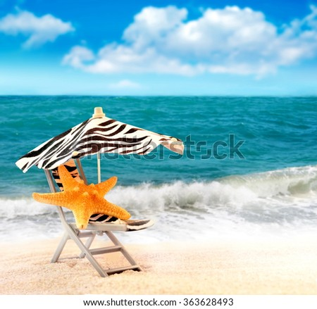 Summer beach. Starfish in chair on the seashore. - stock photo