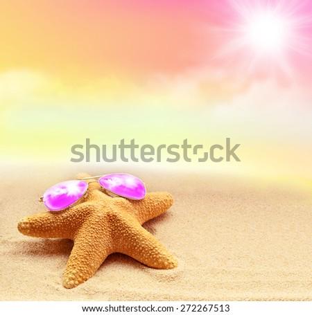 Summer beach. Starfish in pink sunglasses on the seashore. - stock photo