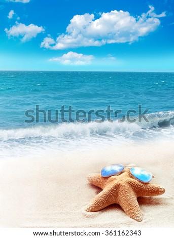 Summer beach. Starfish in sunglasses, ocean and sky. - stock photo