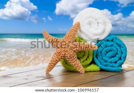Summer beach towels with starfish against ocean background - stock photo