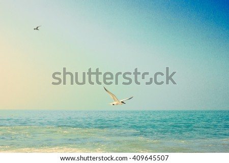 Summer beach with chairs and umbrellas in a soft vintage pastel edition  - stock photo