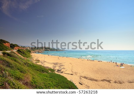 Summer beach with green vegetation and red rocks, Corsica, France - stock photo