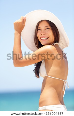 Summer beach woman happy and beautiful with sun hat and lovely big smile standing sideways looking above the viewer with ocean in background. Mixed race Asian Caucasian bikini girl. - stock photo