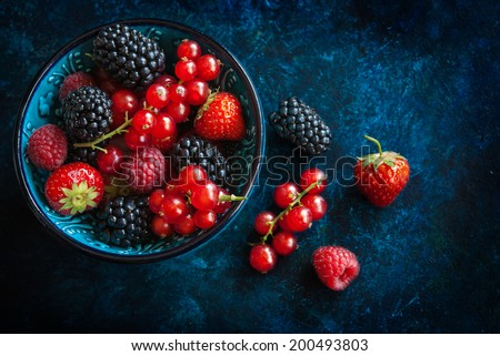 Summer berries in bowl on a table, fruits, raspberry, strawberry, red currant and mulberry - stock photo