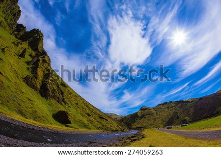Summer blooming Iceland. Camping in valley of canyon Pakgil. The canyon flowing fast shallow creek. The photo was taken Fisheye lens - stock photo